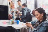 Fotografie žena pomocí smartphone infront lidí s tabletem v kanceláři