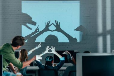 young people playing with shadows after work in modern office
