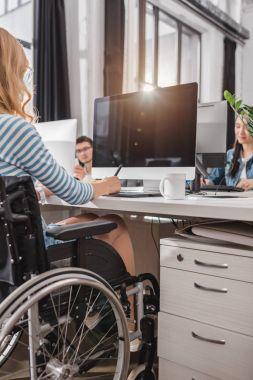 kadının modern ofiste grafik tableti kullanarak tekerlekli sandalyede kırpılmış görüntü