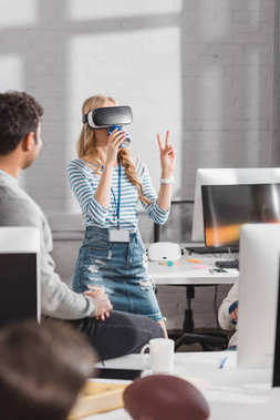 young woman drinking beverage in virtual reality glasses at modern office