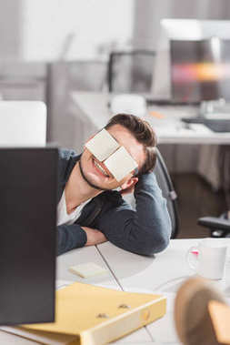 happy man with stickers on eyes at office