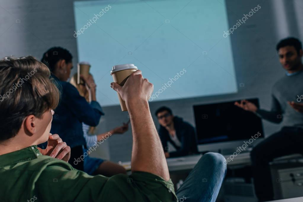cropped image of people in office at nighttime with coffee cups