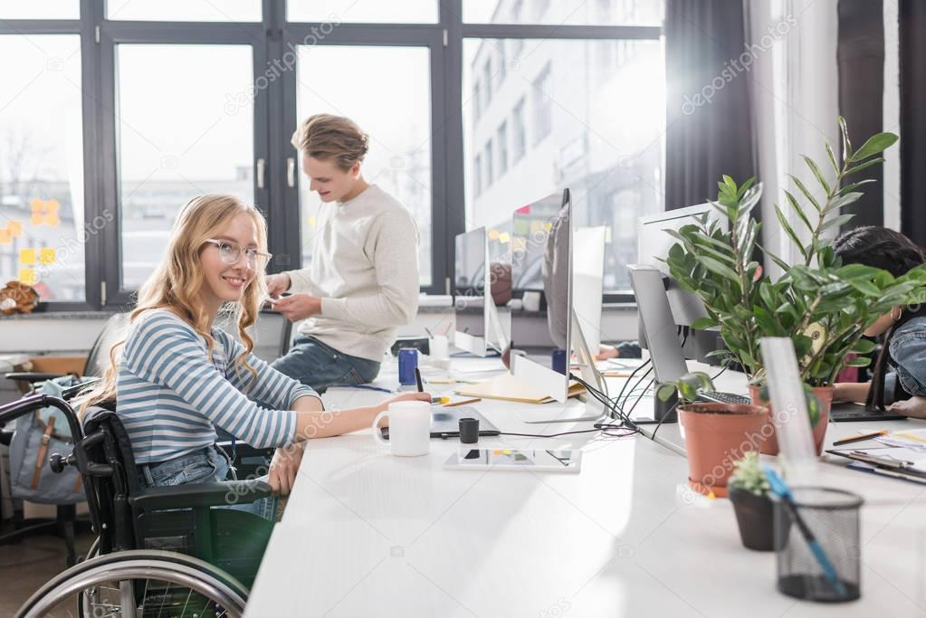 happy incapacitated person in wheelchair working at modern office