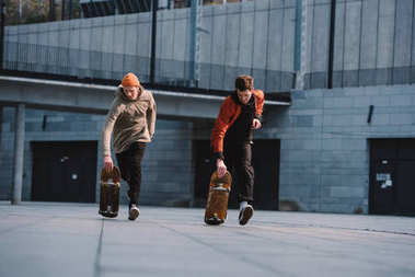 young men in streetwear outfit riding skateboards in urban location