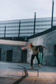professional skateboarder balancing with board on bench in urban location