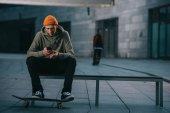 Fotografie skateboardista v moderní Dámské sedí na lavičce a pomocí smartphonu