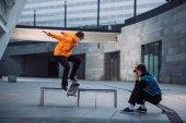 Fotografie Menschen nehmen Foto Skateboarder springen über Bank in innerstädtischer Lage