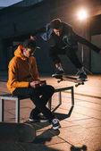 Fotografie Skateboarder springen über Bank während Mann drauf sitzen und Musik hören