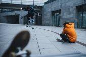 Fotografie man sitzt am Boden und Aufnahme der Skateboarder tun trick