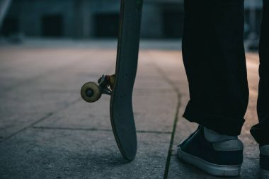 cropped shot of skateboarder standing with board