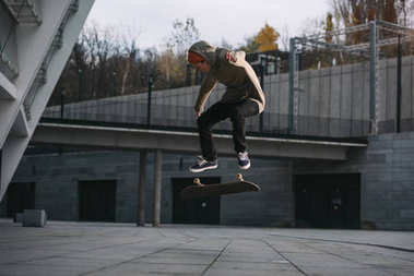 young skateboarder performing jump trick in urban location