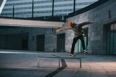 skateboarder balancing with board on bench in urban location