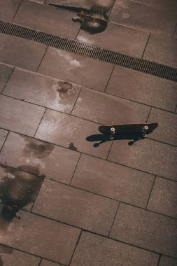high angle view of skateboard laying on floor outdoors