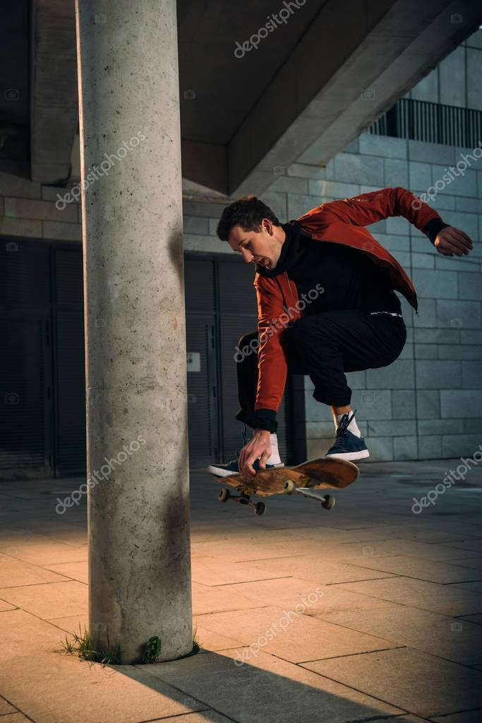handsome young skateboarder performing jump trick in urban location