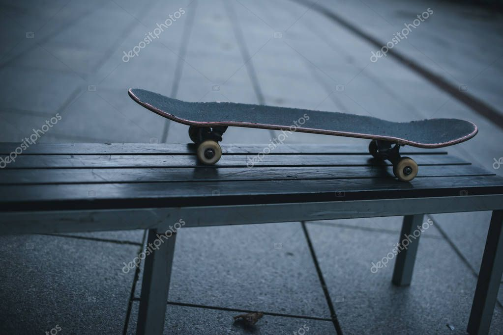 old skateboard standing on bench outdoors