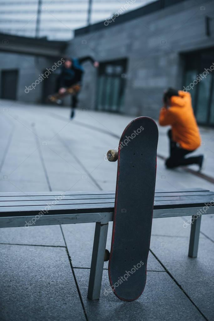 skateboarders taking photos of tricks with skateboard leaning at bench on foreground