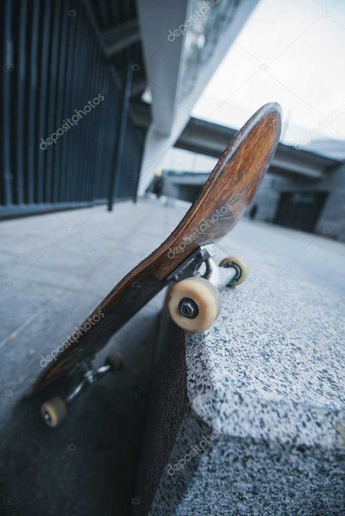 old skateboard leaning at corner of stone wall