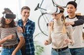Kluci drží vzrušený multikulturní teen dívky dívám na něco s headsety pro virtuální realitu