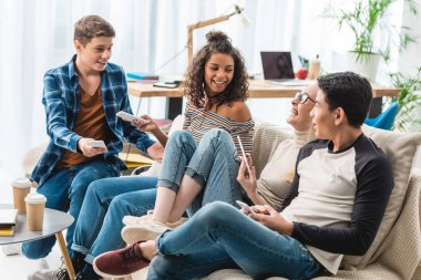 smiling multiethnic teenagers sitting on sofa with gadgets