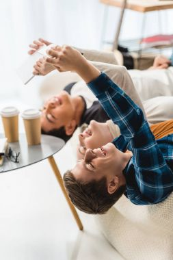 caucasian teenagers lying on sofa and taking selfie with tablet and smartphone