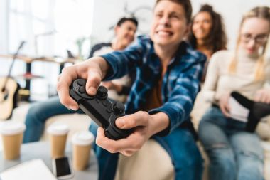 teen boy hardly playing video game and holding joystick