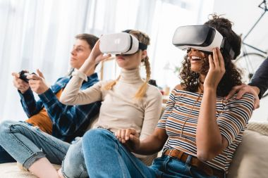 multiethnic teen girls watching something with virtual reality headsets