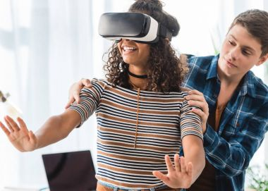 caucasian boy holding african american girl watching something with virtual reality headset