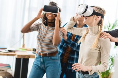 happy multicultural teen girls watching something with virtual reality headsets