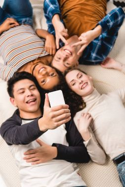 Overhead view of multiethnic teens taking selfie while lying on bed stock vector