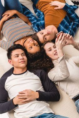 overhead view of multiethnic friends lying on bed and looking at smartphone