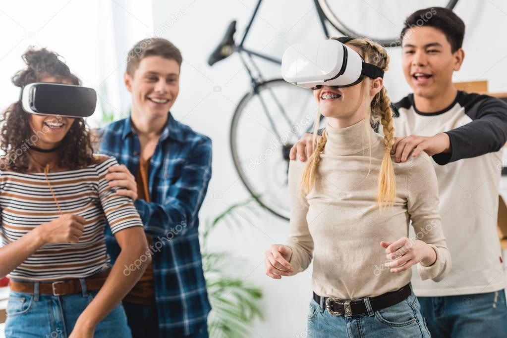 boys holding excited multicultural teen girls watching something with virtual reality headsets