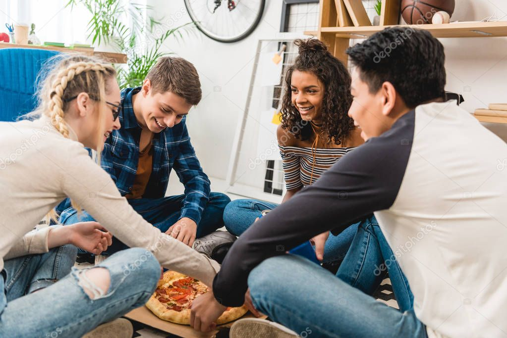 multiethnic teen friends sitting on floor and eating pizza