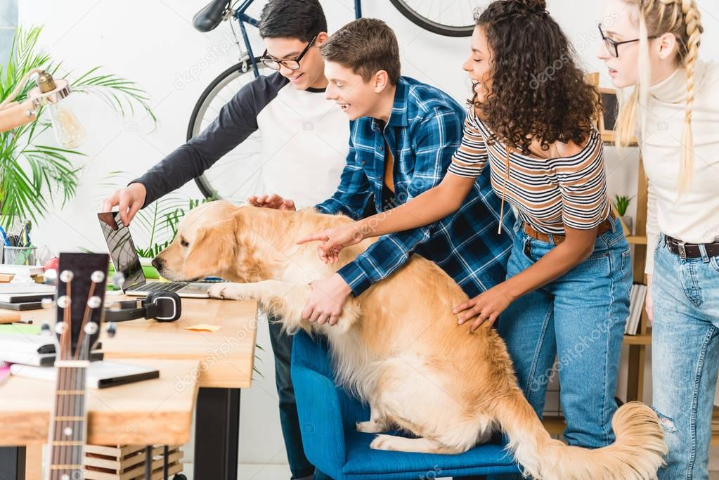 Happy multicultural teenagers showing something on laptop to pet