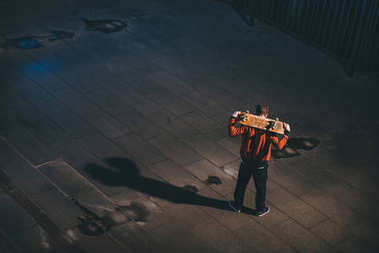 high angle view of skateboarder standing with board on shoulders