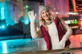 beautiful smiling young woman waving hand and looking away on rink