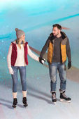 beautiful young couple holding hands and smiling each other while skating on rink