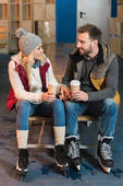 beautiful young couple with coffee to go smiling each other on rink