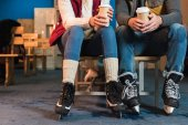 cropped shot of young couple in skates holding coffee to go in paper cups