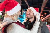 Fotografie glückliches junges Paar in Santa Hüte Lächeln einander auf Eisbahn