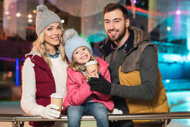 happy family with one child holding paper cups and smiling at camera on rink