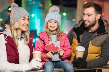 happy parents with coffee to go looking at cute little daughter holding hearts symbol on rink
