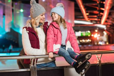 beautiful happy mother and daughter smiling each other on skating rink