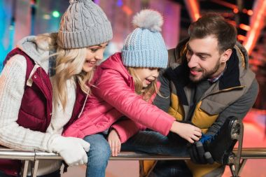 smiling young parents looking at adorable little daughter wearing skates on rink