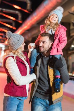 happy young family with adorable little child spending time together on rink