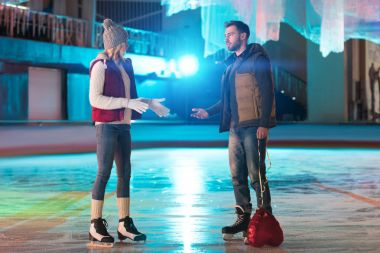 young couple quarreling while man holding heart shaped balloon on rink