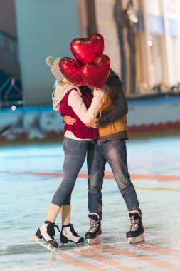 happy young couple with heart shaped balloons hugging on rink at st valentines day