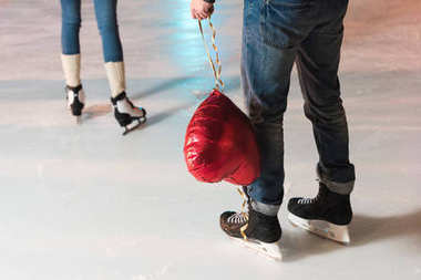 cropped shot of young man holding heart shaped balloon while girlfriend going away on rink