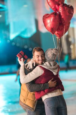 young woman holding gift box and hugging happy boyfriend with heart shaped balloons on rink