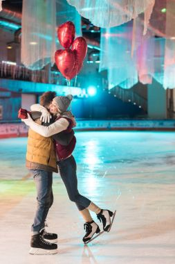 side view of happy young couple with gift box and heart shaped balloons hugging on rink