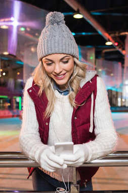 beautiful smiling young woman in earphones using smartphone on rink